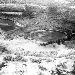 Oblique aerial shot taken circa 1959 as part of the planning for the Perry Lakes stadium complex.  Shot taken looking south, East Lake (to left) and West Lake (to right).  South Lake (now filled in) is visible between and beyond the two larger lakes.  Dead trees are clearly visible in East Lake.  The Plank Road (now Oceanic Drive) in foreground.  An open storm drain is visible crossing the Alderbury Flats.  A cropped portion of this photo appears in Chapter 2 as Plate 2.4a.