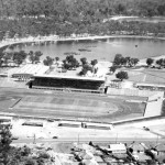 View looking west 1962 across completed stadium.  East Lake (mid ground) has been dredged and banks reformed.  There are a few remnant patches of Baumea articulata.  The causeway built for drag line access to the centre of the lake is still visible.  West Lake (distance) remains untouched.