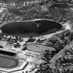 View looking west 1962 across completed stadium.  East Lake (mid ground) has been dredged and banks reformed.  The flood remediation pumping station (refer Chapter 2) is being constructed at the south end of the lake.  There are a few remnant patches of Baumea articulata.  The causeway built for drag line access to the centre of the lake is still visible.  Wetland vegetation in West Lake remains untouched.  Photo appears to have been taken about the same time as Library Board of WA 08.